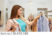 Купить «happy woman choosing clothes at clothing store», фото № 30619188, снято 19 февраля 2016 г. (c) Syda Productions / Фотобанк Лори
