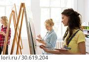 Купить «woman with easel painting at art school studio», фото № 30619204, снято 26 мая 2017 г. (c) Syda Productions / Фотобанк Лори