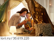 Купить «happy family with smartphone in kids tent at home», фото № 30619220, снято 27 января 2018 г. (c) Syda Productions / Фотобанк Лори