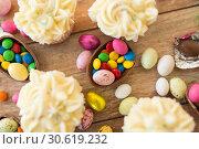 Купить «cupcakes with chocolate eggs and candies on table», фото № 30619232, снято 15 марта 2018 г. (c) Syda Productions / Фотобанк Лори