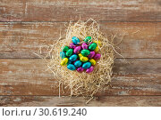 Купить «chocolate eggs in foil wrappers in straw nest», фото № 30619240, снято 22 марта 2018 г. (c) Syda Productions / Фотобанк Лори