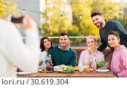 Купить «happy friends photographing at rooftop party», фото № 30619304, снято 2 сентября 2018 г. (c) Syda Productions / Фотобанк Лори