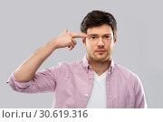Купить «bored man making headshot by finger gun gesture», фото № 30619316, снято 3 февраля 2019 г. (c) Syda Productions / Фотобанк Лори