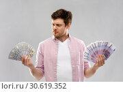 Купить «uncertainy man with fans of euro and dollar money», фото № 30619352, снято 3 февраля 2019 г. (c) Syda Productions / Фотобанк Лори
