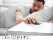 Купить «sleepy young man reaching for smartphone in bed», фото № 30619412, снято 6 мая 2017 г. (c) Syda Productions / Фотобанк Лори