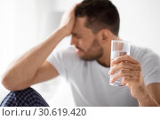 Купить «close up of sick man with glass of water», фото № 30619420, снято 6 мая 2017 г. (c) Syda Productions / Фотобанк Лори