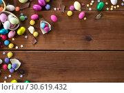 Купить «chocolate eggs and candy drops on wooden table», фото № 30619432, снято 22 марта 2018 г. (c) Syda Productions / Фотобанк Лори