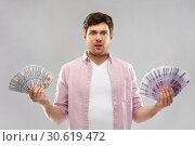 Купить «confused young man with euro and dollar money», фото № 30619472, снято 3 февраля 2019 г. (c) Syda Productions / Фотобанк Лори
