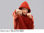 Купить «man in red hoodie fighting with fists or boxing», фото № 30619480, снято 3 февраля 2019 г. (c) Syda Productions / Фотобанк Лори