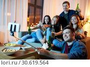 Купить «friends taking picture by selfie stick at home», фото № 30619564, снято 22 декабря 2018 г. (c) Syda Productions / Фотобанк Лори