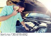 Купить «man with broken car calling on smartphone», фото № 30619692, снято 12 июня 2016 г. (c) Syda Productions / Фотобанк Лори