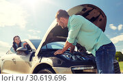couple with open hood of broken car at countryside. Стоковое фото, фотограф Syda Productions / Фотобанк Лори