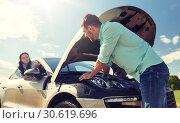 Купить «couple with open hood of broken car at countryside», фото № 30619696, снято 12 июня 2016 г. (c) Syda Productions / Фотобанк Лори