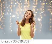 Купить «happy teenage girl with two sparklers over lights», фото № 30619708, снято 29 января 2019 г. (c) Syda Productions / Фотобанк Лори