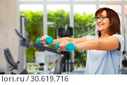 happy old woman with dumbbells exercising in gym. Стоковое фото, фотограф Syda Productions / Фотобанк Лори