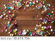 Купить «chocolate eggs and candy drops on wooden table», фото № 30619756, снято 22 марта 2018 г. (c) Syda Productions / Фотобанк Лори