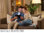 Купить «happy couple using tablet pc at home in evening», фото № 30619780, снято 5 января 2019 г. (c) Syda Productions / Фотобанк Лори