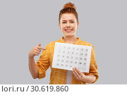 happy red haired teenage girl with calendar sheet. Стоковое фото, фотограф Syda Productions / Фотобанк Лори