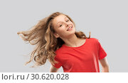 smiling teenage girl in red with long wavy hair. Стоковое фото, фотограф Syda Productions / Фотобанк Лори