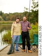 Купить «friends with fishing rods and net at lake or river», фото № 30620100, снято 8 сентября 2018 г. (c) Syda Productions / Фотобанк Лори