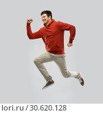 Купить «young man in hoodie jumping over grey background», фото № 30620128, снято 3 февраля 2019 г. (c) Syda Productions / Фотобанк Лори