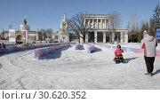 Купить «Children's attraction in the park VDNH. Children ride electric cars and snowmobiles.», видеоролик № 30620352, снято 16 февраля 2019 г. (c) Андрей Радченко / Фотобанк Лори