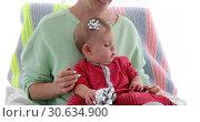 Купить «Mother decorates baby's head with packing bows», видеоролик № 30634900, снято 1 апреля 2019 г. (c) Ekaterina Demidova / Фотобанк Лори