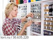 Купить «Female next to shelf with buttons», фото № 30635220, снято 23 мая 2019 г. (c) Яков Филимонов / Фотобанк Лори