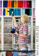Купить «portrait of female cashier standing at cash desk in embroidery shop», фото № 30635232, снято 25 апреля 2019 г. (c) Яков Филимонов / Фотобанк Лори