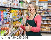 Купить «Mature saleswoman giving thumbs up in supermarket», фото № 30635304, снято 8 февраля 2019 г. (c) Яков Филимонов / Фотобанк Лори