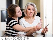 Купить «Upset women using smartphone», фото № 30635316, снято 2 марта 2019 г. (c) Яков Филимонов / Фотобанк Лори