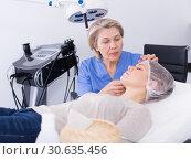 Купить «Cosmetician examining face skin of girl», фото № 30635456, снято 16 марта 2018 г. (c) Яков Филимонов / Фотобанк Лори