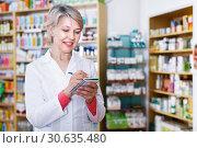 Купить «Female seller noting assortment in organic shop», фото № 30635480, снято 15 марта 2017 г. (c) Яков Филимонов / Фотобанк Лори