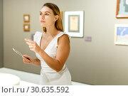 Купить «Woman observing museum exposition», фото № 30635592, снято 28 июля 2018 г. (c) Яков Филимонов / Фотобанк Лори