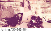 Купить «Pregnant woman carefully choosing infant car seat in kids mall», фото № 30643984, снято 22 сентября 2017 г. (c) Яков Филимонов / Фотобанк Лори