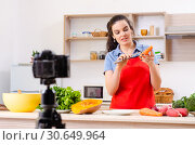 Купить «Young female vegetarian recording video for her blog», фото № 30649964, снято 22 февраля 2019 г. (c) Elnur / Фотобанк Лори