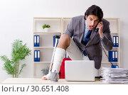 Купить «Leg injured employee working in the office», фото № 30651408, снято 15 января 2019 г. (c) Elnur / Фотобанк Лори