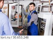 Купить «Workman showing PVC manufacturing output», фото № 30653248, снято 30 марта 2017 г. (c) Яков Филимонов / Фотобанк Лори