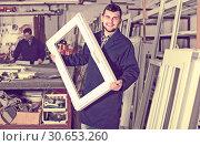Купить «Workman is demonstrating PVC manufacturing output», фото № 30653260, снято 30 марта 2017 г. (c) Яков Филимонов / Фотобанк Лори