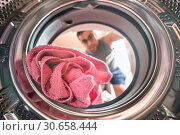 Young man doing laundry view from the inside of washing machine. Стоковое фото, фотограф David Herraez Calzada / easy Fotostock / Фотобанк Лори