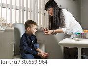 Купить «Медсестра вскрывает бактерицидный лейкопластырь для оказания медицинской помощи мальчику при порезе», фото № 30659964, снято 17 марта 2019 г. (c) Наталья Гармашева / Фотобанк Лори