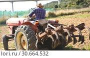 Купить «man working on tractor at farm field», видеоролик № 30664532, снято 12 апреля 2019 г. (c) Яков Филимонов / Фотобанк Лори