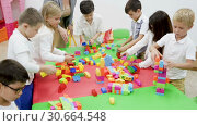 Купить «Group of schoolkids playing with toy bricks in circle with their cheerful female teacher», видеоролик № 30664548, снято 18 декабря 2018 г. (c) Яков Филимонов / Фотобанк Лори