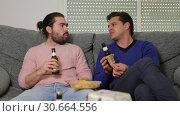 Купить «Two men friends are talking and drinking beer», видеоролик № 30664556, снято 13 марта 2019 г. (c) Яков Филимонов / Фотобанк Лори