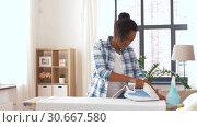 Купить «african american woman ironing bed linen at home», видеоролик № 30667580, снято 15 апреля 2019 г. (c) Syda Productions / Фотобанк Лори
