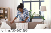 Купить «african american woman arranging sofa cushions», видеоролик № 30667596, снято 15 апреля 2019 г. (c) Syda Productions / Фотобанк Лори