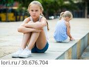 Купить «Small sisters upset after quarrel outside», фото № 30676704, снято 20 июля 2017 г. (c) Яков Филимонов / Фотобанк Лори