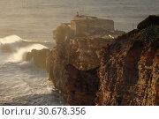 Купить «PORTUGAL Nazare -- 04 Jan 2015 -- Since professional surfers began breaking records in 2011, the Farol da Nazare (Nazare lighthouse) situated on the Forte...», фото № 30678356, снято 19 января 2015 г. (c) age Fotostock / Фотобанк Лори
