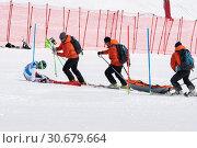 Купить «Спасатели Камчатского спасательного отряда на горных лыжах с носилками едут для оказания первой медицинской помощи и эвакуации горнолыжника во время Чемпионата России по горным лыжам», фото № 30679664, снято 28 марта 2019 г. (c) А. А. Пирагис / Фотобанк Лори
