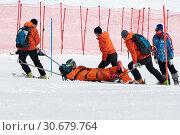 Купить «Спасатели Камчатского спасательного отряда эвакуируют пострадавшего (получившего травму) горнолыжника со склона горы на спасательных носилках во время Чемпионата России по горным лыжам», фото № 30679764, снято 28 марта 2019 г. (c) А. А. Пирагис / Фотобанк Лори